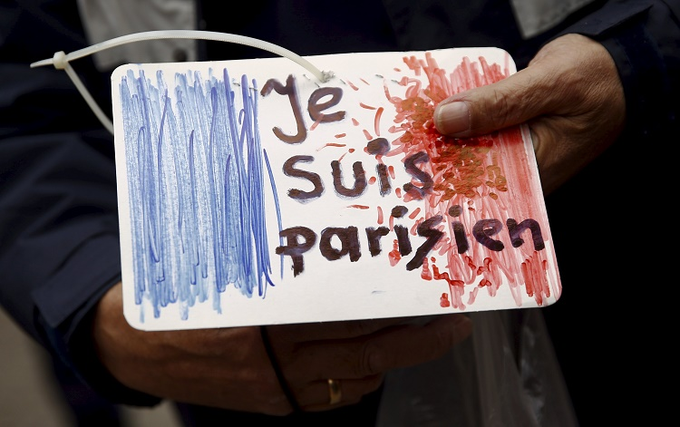 """A man holds a drawing depicting the French flag and carrying the words """"I am Parisian"""" in front of the French embassy after attacks in Paris on Friday, in Warsaw, Poland November 14, 2015. REUTERS/Kacper Pempel"""